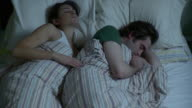 MS HA Young couple spooning in bed, woman unable to fall asleep turning / Brooklyn, New York City, New York, USA