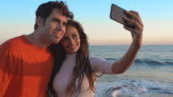 Young couple standing beach in sunset taking photograph