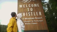 MS Young couple standing in front of welcome to Whistler sign / Whistler, British Columbia, Canada