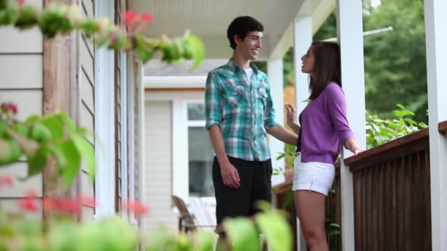 MS R/F Young couple standing on porch of vacation home in discussion smiling/Washington, USA