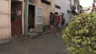 WS PAN Young couple strolling down city backstreet, looking at dog barking, Bangkok, Thailand