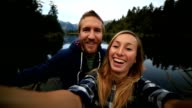 Young couple take a selfie portrait by the lake