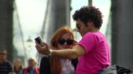 MS TU Young couple take pictures and kiss on the Brooklyn bridge/ New York City