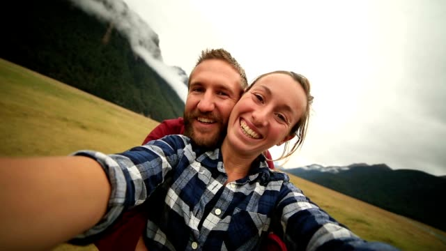 Young couple take selfie portrait with mountain landscape