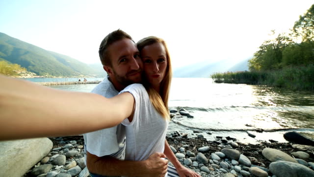 Young couple taking cell phone picture by the lake