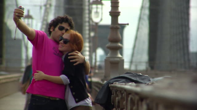 MS Young couple taking photo of themselves kissing on the Brooklyn Bridge/ New York City