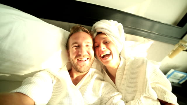 Young couple taking selfie in hotel bed