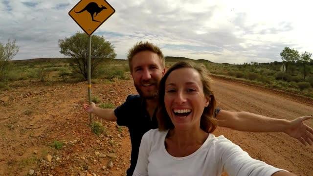 Young couple taking selfie with kangaroo sign, Australia