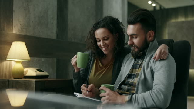 Young couple talking and writing