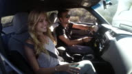 MS POV Young couple talking, smiling, laughing, having fun while driving in car / Venice, California, United States