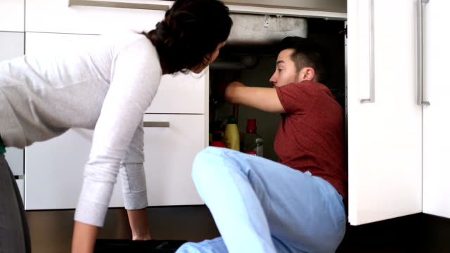 Young couple talking while repairing sink