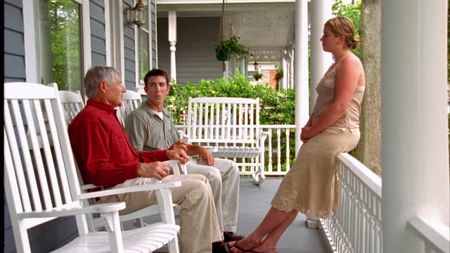 A young couple talks with a retiree on his front porch.