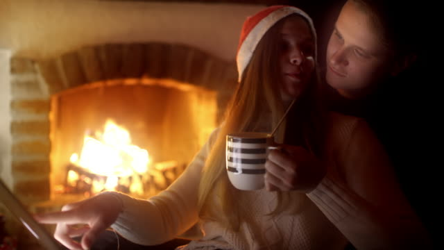 DS Young couple using a laptop by the fireplace on a Christmas Eve