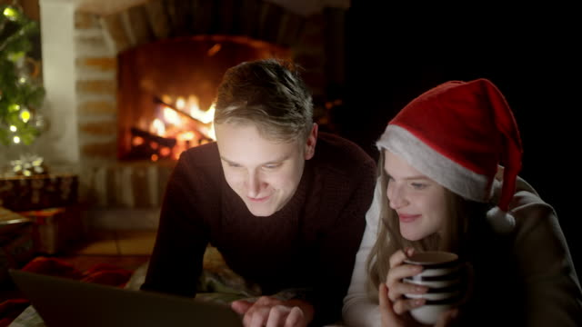 DS Young couple using a laptop on a Christmas night