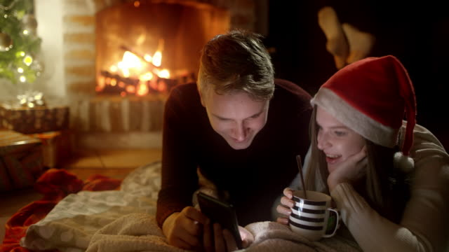 DS Young couple using a smartphone by the fireplace on a Christmas night