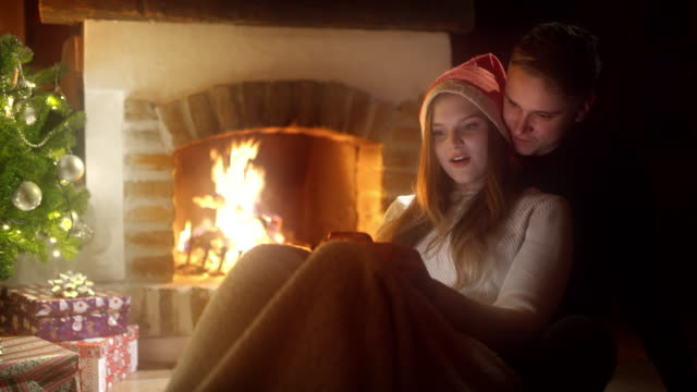 DS Young couple using smartphones by the fireplace on a Christmas Eve