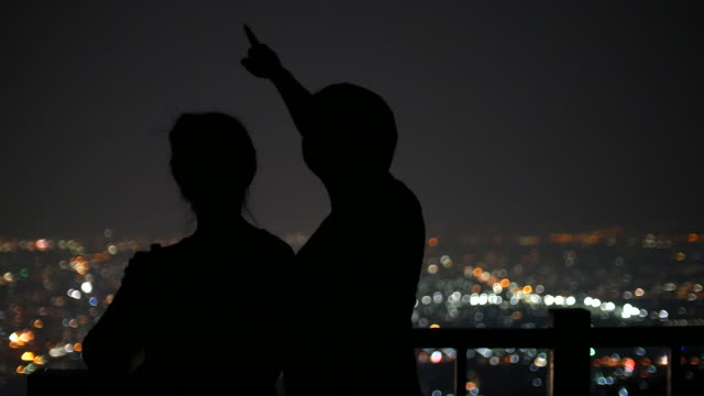 Young Couple viewing Stars on the background of the city at night urban scene, 4k(UHD)