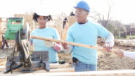 Young couple volunteers working together on home built for charity