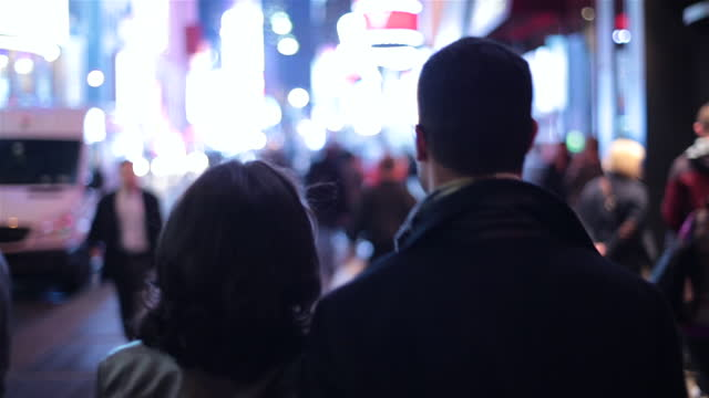 Young couple walk arm-in-arm down busy streets and sidewalks towards the heart of Times Square