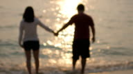 Young Couple Walking on Beach to the sea holding hands at sunset time ,Blurred motion ,relaxation concept