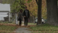 WS PAN MS Young couple walking on sidewalk in Autumn / Provo, Utah, USA