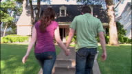 WS, Young couple walking towards brick suburban house, rear view, Dallas, Texas, USA