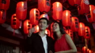 MS young couple walking under Chinese lanterns at night.