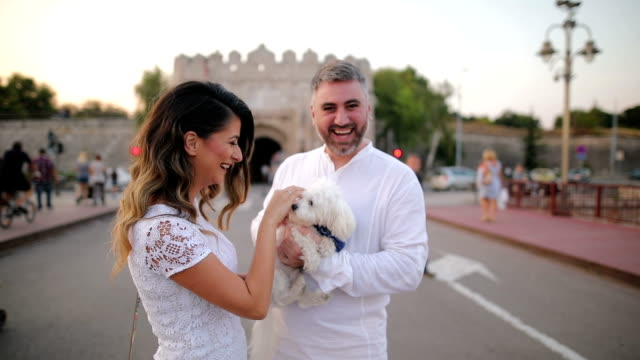 Young couple walking with maltese dog