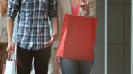 SLO MO young couple walking with shopping bags