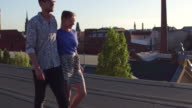 A young couple walks arm in arm on an urban rooftop