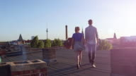 A young couple walks hand in hand on an urban rooftop