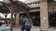 A young couple walks through the door of a coffee shop