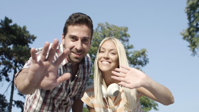 Young Couple Waving To The Camera