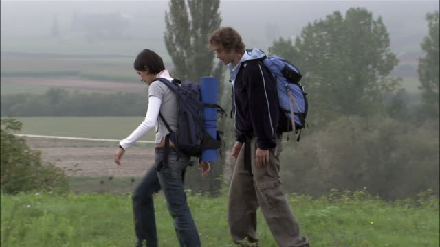 Young couple wearing backpacks hitchiking on roadside / running after car
