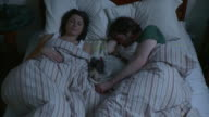 MS HA Young couple with puppy sleeping in bed / Brooklyn, New York City, New York, USA