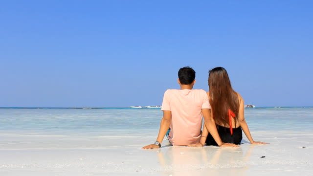 Young couple with white sand beach