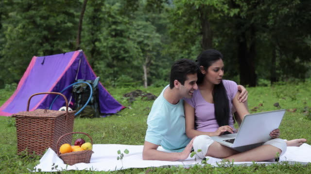 Young couple working on a laptop in a forest, Malshej Ghat, Maharashtra, India