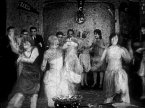 B/W 1926 young couples dancing Charleston indoors (college party) / newsreel