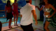 Young couples enjoy salsa dancing in a moonlit nightclub. Available in HD.
