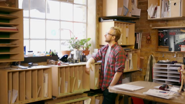 Young creative professional looks out of window in modern office space.