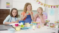 3 young cute girls getting ready for birthday party in the kitchen