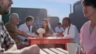 Junge Ärzte diskutieren Fall mit Digital-Tablette am Krankenhaus Café im freien