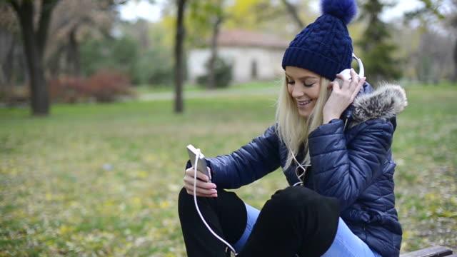 Elegante junge Frau hört ihre Musik im park