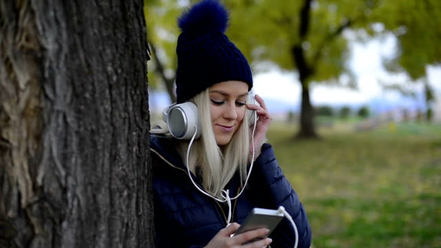 Young elegant female listens to her music in the park