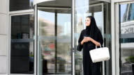 Young Emirati woman by the revolving door