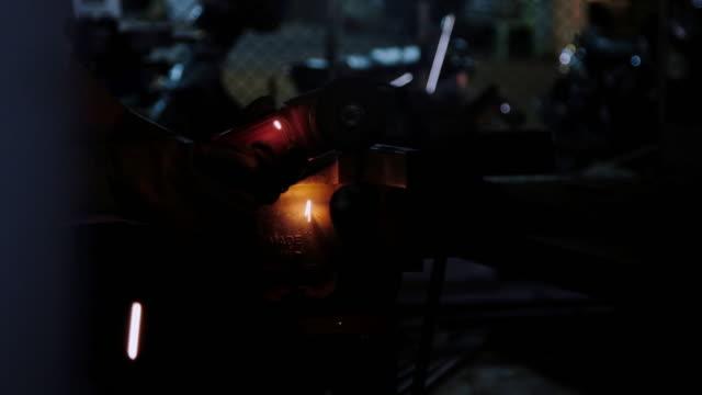 Unga engineering karriär koncept. Stilig ung ingenjör i workshop med cirkulär metall cutter slipning stål. Kinesiska arbetare med handskar i verklig mekanisk verkstad. Massor av spark och flash.