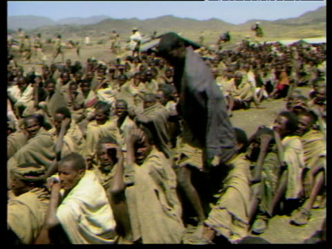 Young Ethiopian man putting on jacket from Europe given as charitable donation Oct 84