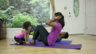 Young ethnic family exercising at home