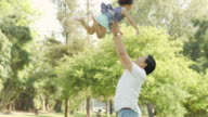 Young ethnic father playing with his baby girl throwing her in the air