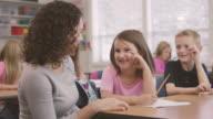 Giovane etnico lavora con il suo insegnante di scuola elementare studenti in classe